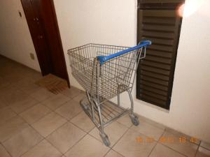 Morador descumpre regra do condomínio e deixa carrinho no corredor para vigilane noturno ir buscá-lo.