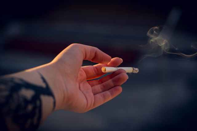 close up photography of a person holding cigarette